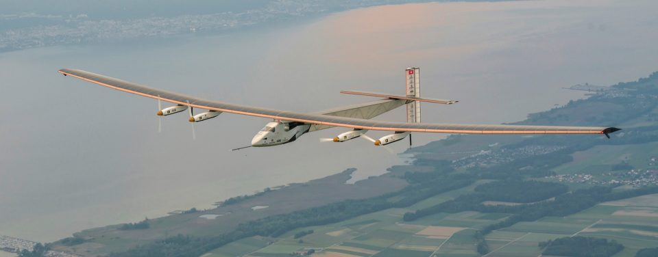 Front view of Solar Impulse plane flying over a river - Solar Impulse Around the World flight, 2015